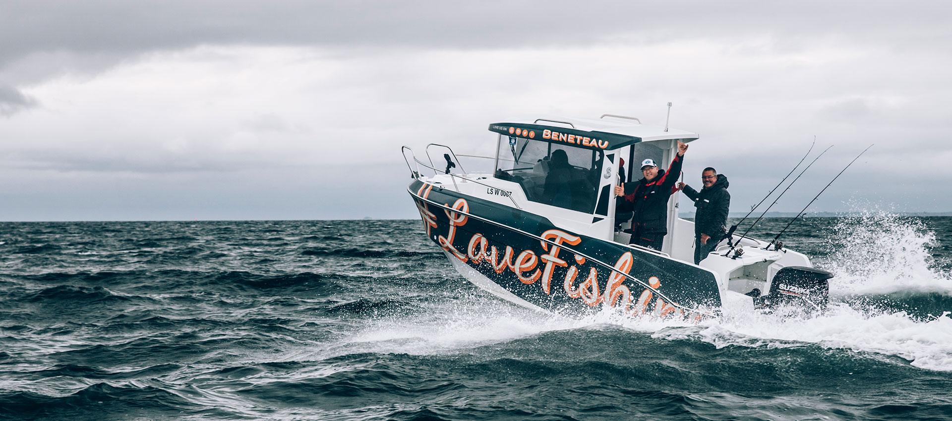 Eine Beneteu Barracuda 9 mit zwei grüßenden Anglern und Schriftzug